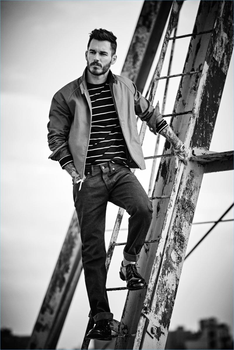 Posing on a ladder, David Alexander Flinn wears a Todd Snyder long-sleeve striped tee $98, Harrington jacket $328, and selvedge denim jeans $198.