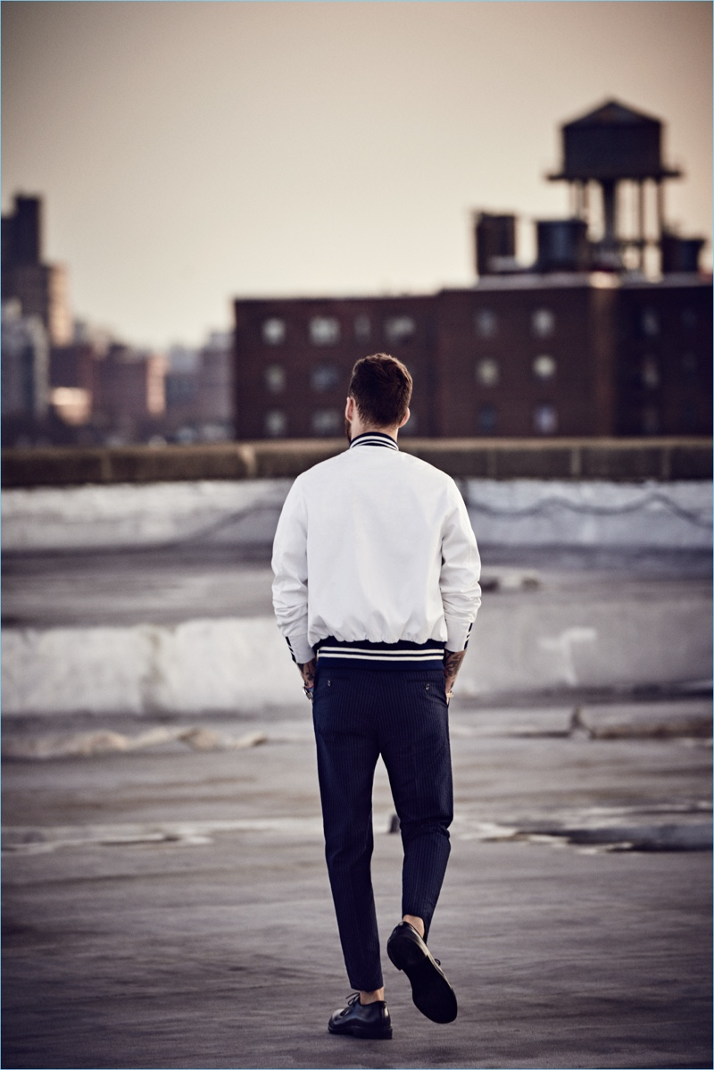 Walking away from the camera, David Alexander Flinn wears a white Todd Snyder + Champion bomber jacket $348 and Japanese selvedge chino officer pant $198.
