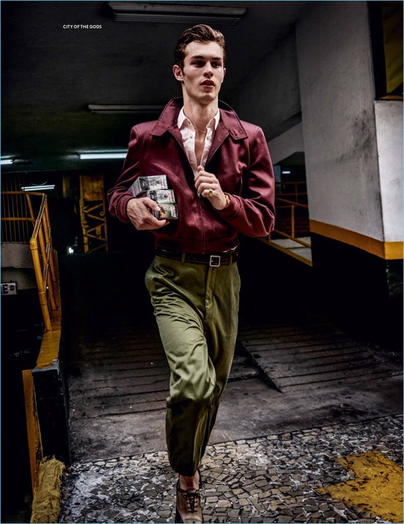 On the move, Kit Butler wears a bomber jacket, shirt, and chinos by Balenciaga with Salvatore Ferragamo shoes.