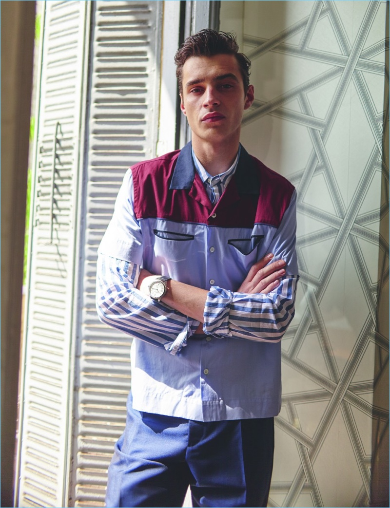 Crossing his arms, Adrien Sahores wears a striped Wrangler shirt with an Andrea Pompilio short-sleeve shirt. The French model also wears Salvatore Ferragamo trousers and a Hamilton watch.