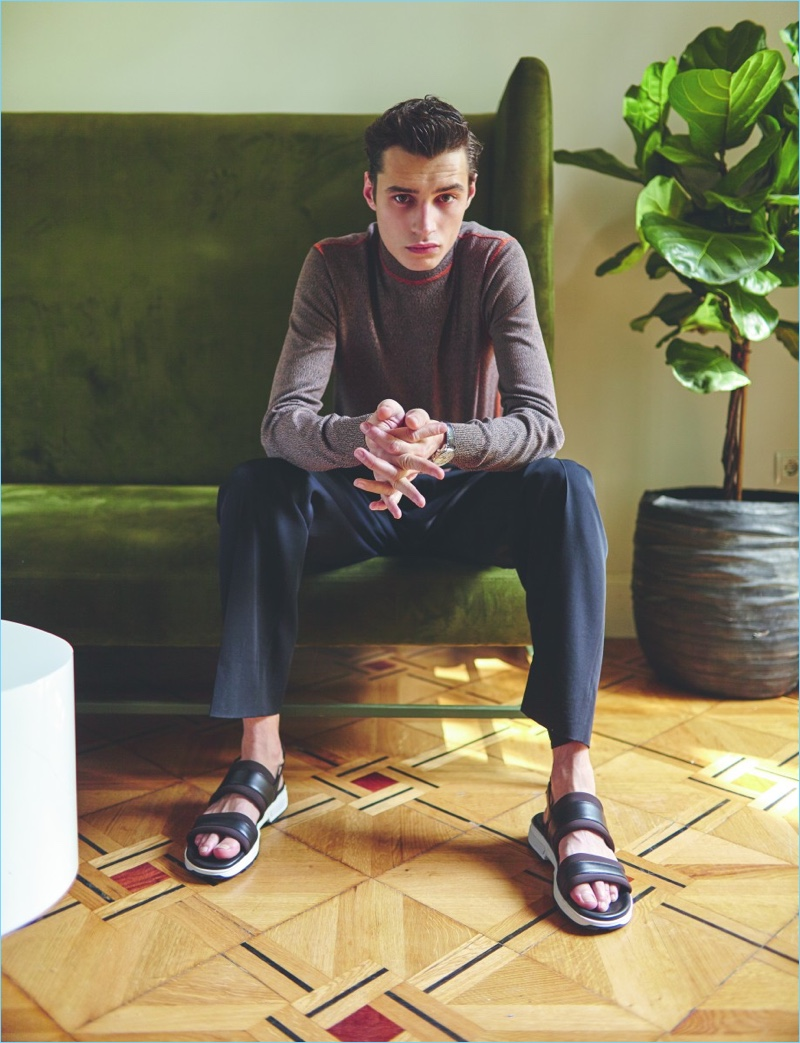 Front and center, Adrien Sahores sports a Prada sweater with Bottega Veneta trousers, Hermes sandals, and a Longines watch.