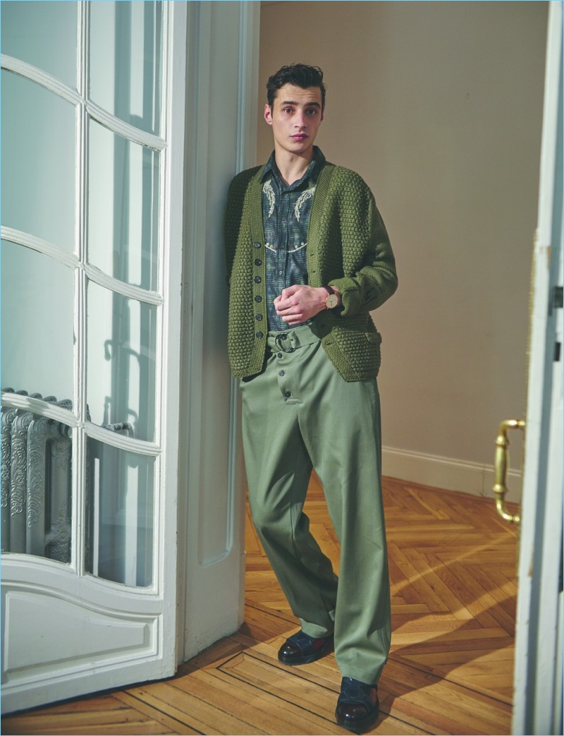 A smart vision, Adrien Sahores wears a green Loewe cardigan sweater with a Missoni shirt. The leading model also rocks Emporio Armani trousers and Salvatore Ferragamo shoes with a Tissot watch.