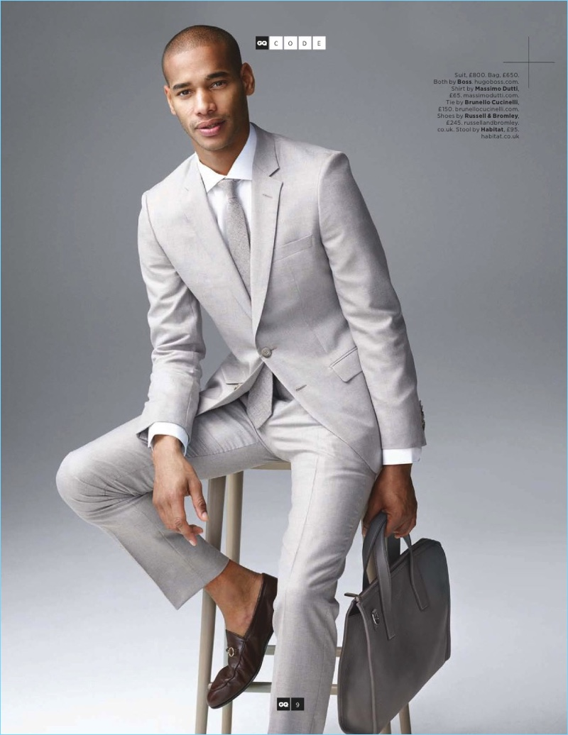Front and center, Sacha M'Baye models a pale grey suit and bag by BOSS Hugo Boss. The French model also wears a Brunello Cucinelli tie and Russell & Bromley shoes.