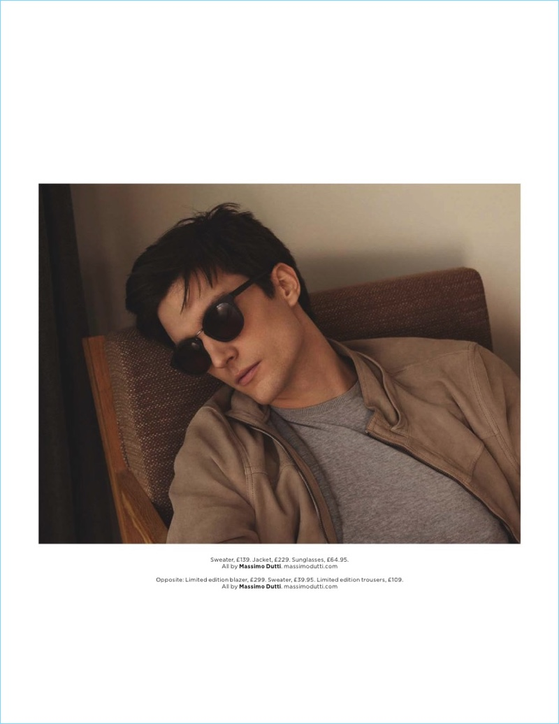 Catching a moment to relax, Charlie Timms sports a sweater, jacket, and sunglasses from Massimo Dutti.