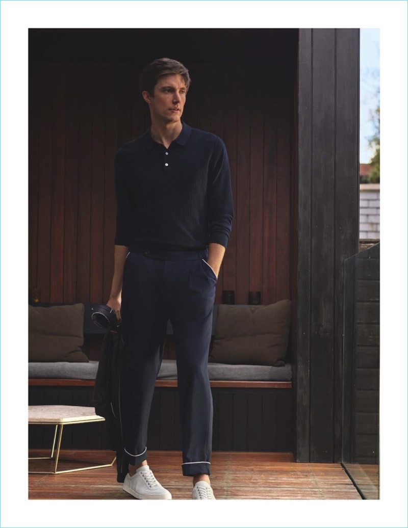 Sporting a navy look, Charlie Timms wears a Massimo Dutti knit polo and trousers detailed with white piping. The British model also rocks white sneakers.