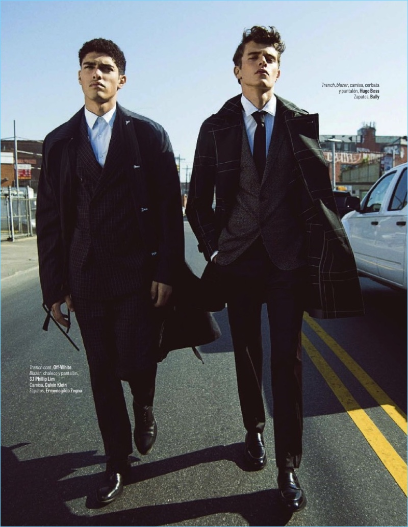 Left to Right: Torin Verdone models an Off-White trench coat with a 3.1 Phillip Lim suit, Calvin Klein shirt, and Ermenegildo Zegna shoes. Jordy Baan sports a Hugo Boss look with Bally shoes.