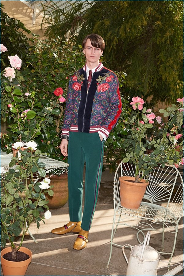 Modern dandy style reigns with a Gucci heart embroidered shirt $640 and velvet and paisley print bomber jacket $3,350. The outfit comes together with Gucci trousers $1,150, leather Chelsea boots $980, and a tie $200.