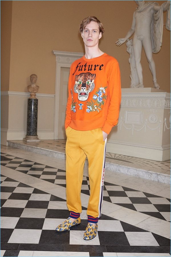Italian fashion house Gucci brings color to the season with its embroidered tiger sweater $2,450, striped jersey sweatpants $920, and printed satin loafers $650.