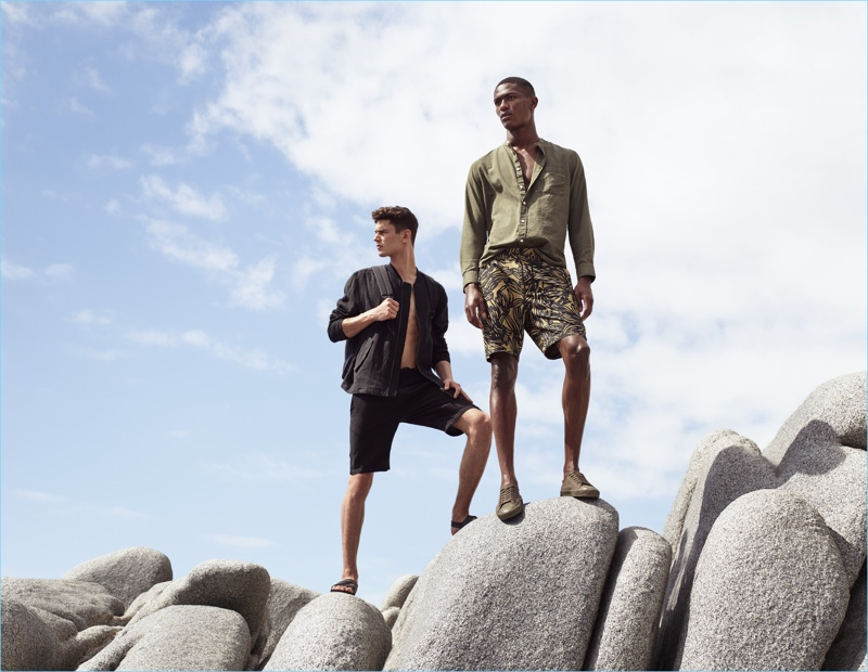 Left to Right: Arthur Gosse wears a linen bomber jacket $59.99 with knee-length cotton shorts $24.99, and sandals $24.99. Hamid Onifade sports a collarless shirt $34.99 and patterned knee-length shorts $24.99 with sneakers.