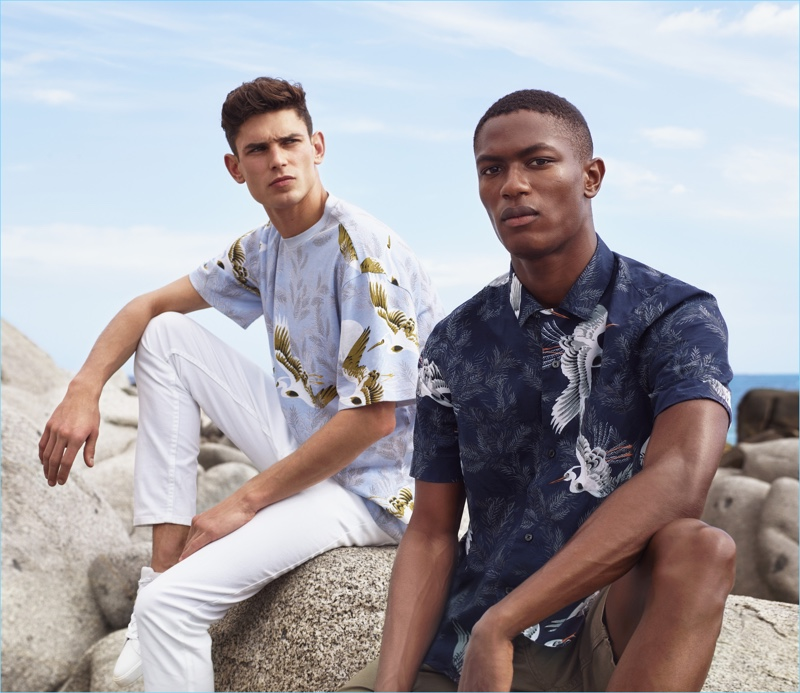 Left to Right: Arthur Gosse wears an oversized graphic t-shirt with white skinny fit twill pants $29.99 and sneakers $24.99. Hamid Onifade rocks a resort shirt $24.99 and short cotton shorts $24.99.