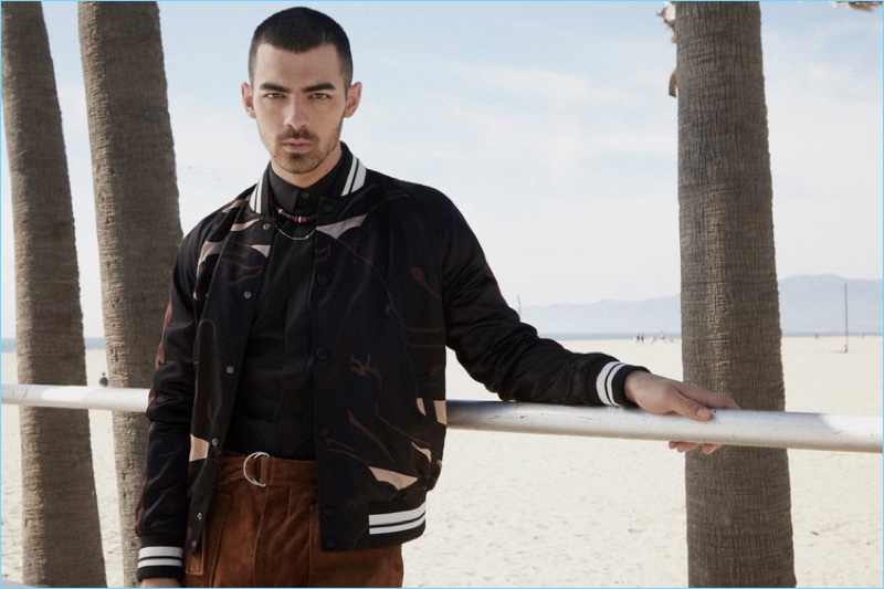 Singer Joe Jonas wears a Valentino bomber jacket with a Dior Homme shirt and necklace. Jonas also sports 3.1 Phillip Lim trousers.