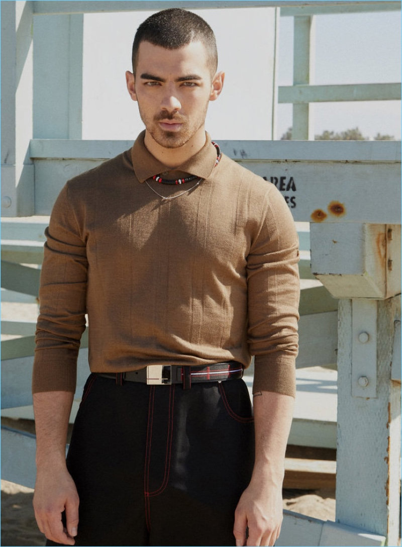 Embracing a brown and black color palette, Joe Jonas wears an Ermenegildo Zegna Couture polo. Jonas also sports jeans, a belt, and necklace by Dior Homme.
