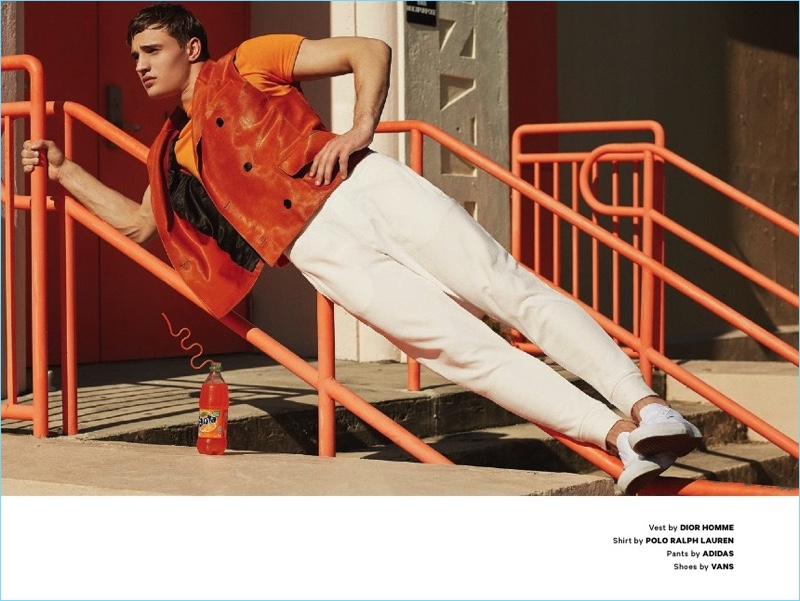 Sporting an orange look, Julian Schneyder dons a Dior Homme vest with a POLO Ralph Lauren shirt. The Austrian model also wears Adidas pants and Vans shoes.