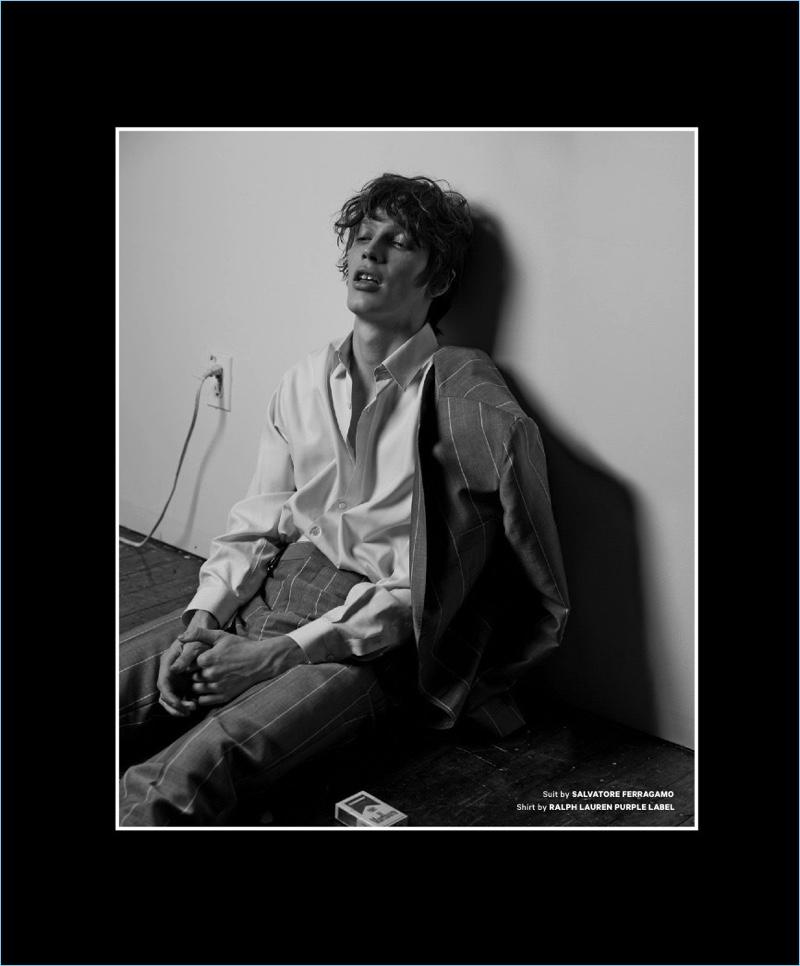 Sitting, Lucas Satherley wears a striped Salvatore Ferragamo suit with a Ralph Lauren Purple Label shirt.