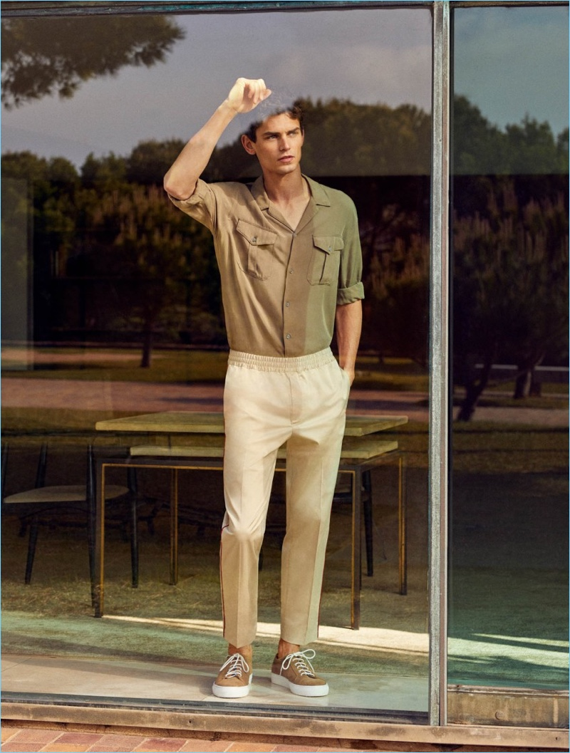 Embracing summer neutrals, Arthur Gosse sports a Mango Man chest pocket shirt $69.99, contrast trim trousers $69.99, and lace-up suede sneakers $99.99.