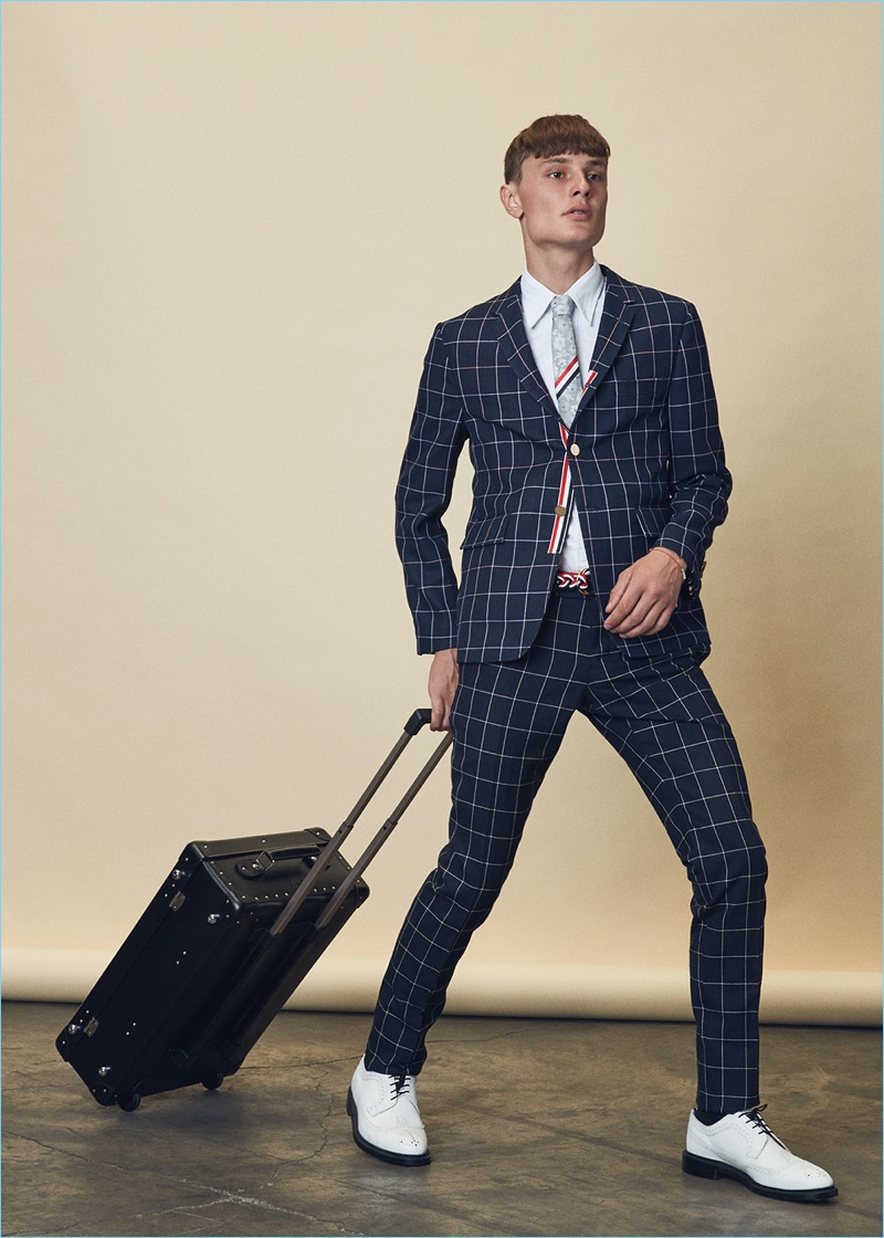 """Suiting up, Vanya dons a Thom Browne windowpane blazer $1,608 and trousers $867 with a classic short-sleeve button-down $425. He also wears Thom Browne white leather brogues $1,250, a floral silk jacquard tie $240, and a nantucket braided rope D ring belt $390. Vanya carries a Globe-Trotter 21"""" original trolley case $1,370 as well."""