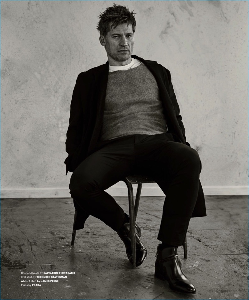 Sitting for a portrait, Nikolaj Coster-Waldau wears a coat and boots by Salvatore Ferragamo. Coster-Waldau also sports a t-shirt from The Elder Statesman, a James Perse t-shirt, and Prada trousers.