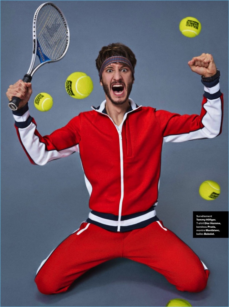 Posing for a cheeky image, Pierre Niney rocks a Tommy Hilfiger tracksuit with a Dior Homme tee, and Prada headband.