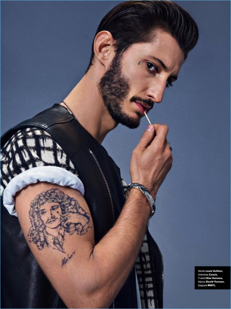 Channeling his inner bad boy, Pierre Niney wears a Louis Vuitton leather vest with a graphic Coach t-shirt.