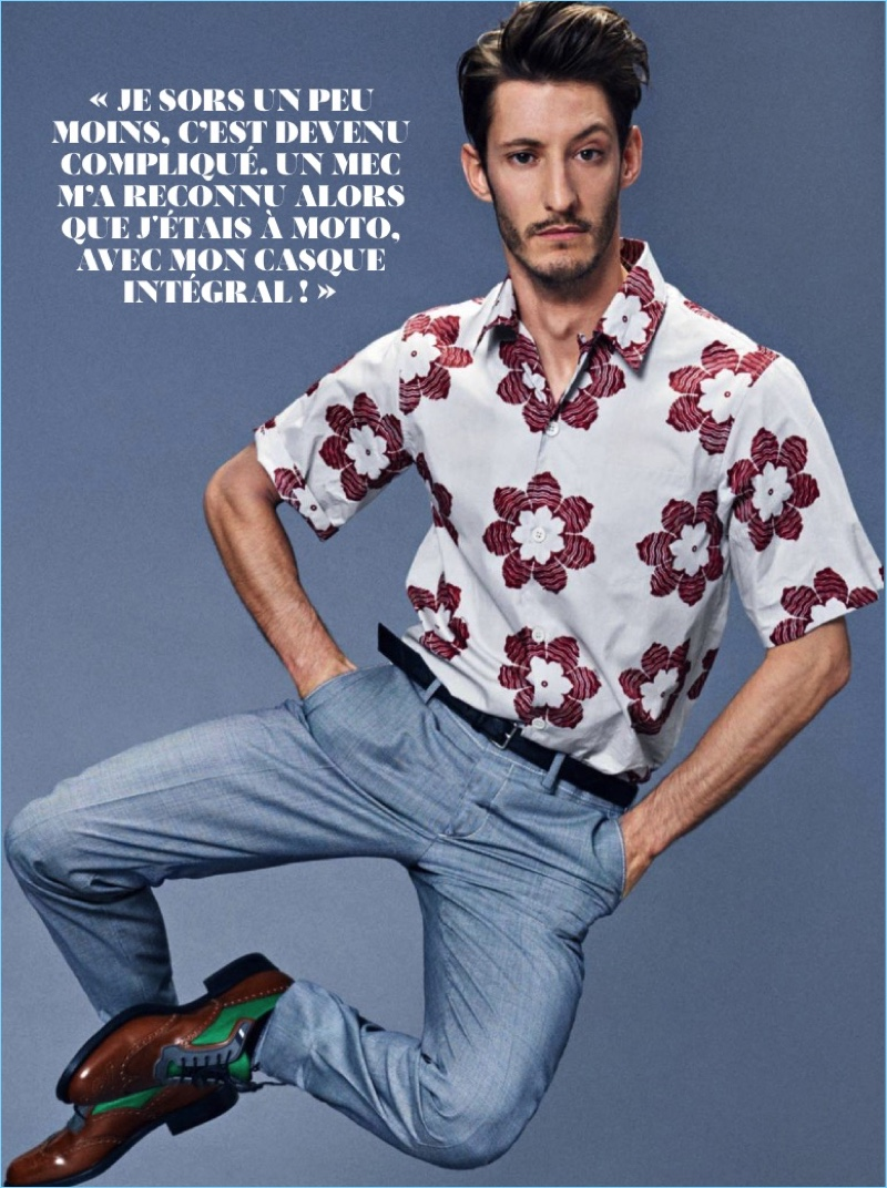 Embracing classic summer style, Pierre Niney dons a shirt, trousers, belt, and shoes by Prada.