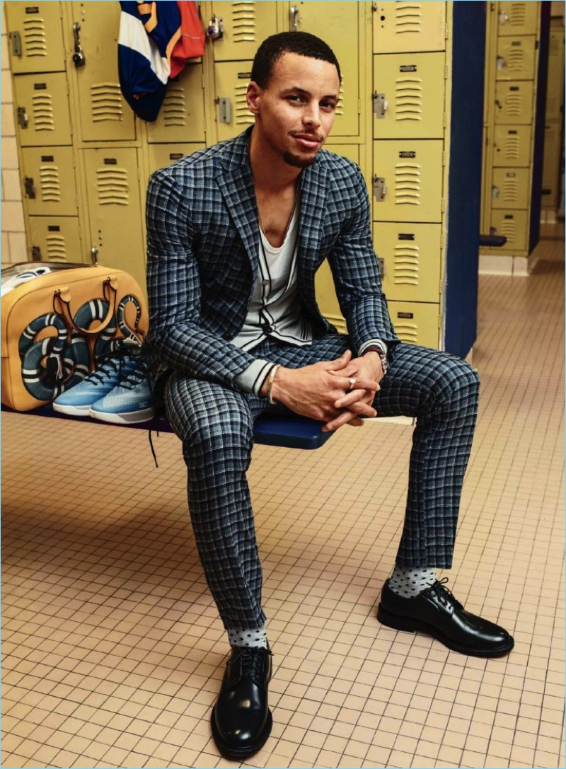 Posing for a photo in the locker room, Steph Curry dons a Boglioli suit with a Hermes cardigan and tank. Curry also wears Church's shoes, and Etiquette Clothiers socks.