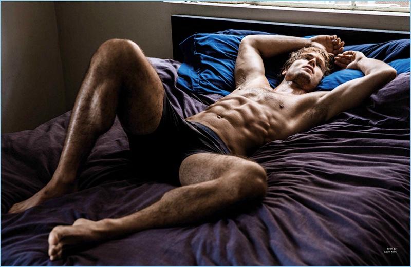 Laying in bed shirtless, Chad James Buchanan wears Calvin Klein underwear.