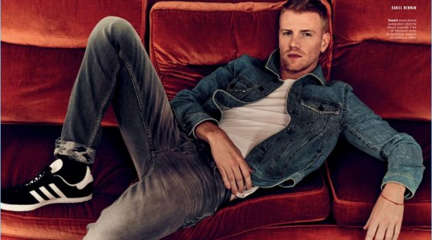Relaxing, Daniel Newman wears a t-shirt and denim jacket by Diesel. He also sports 7 For All Mankind jeans and Adidas sneakers.