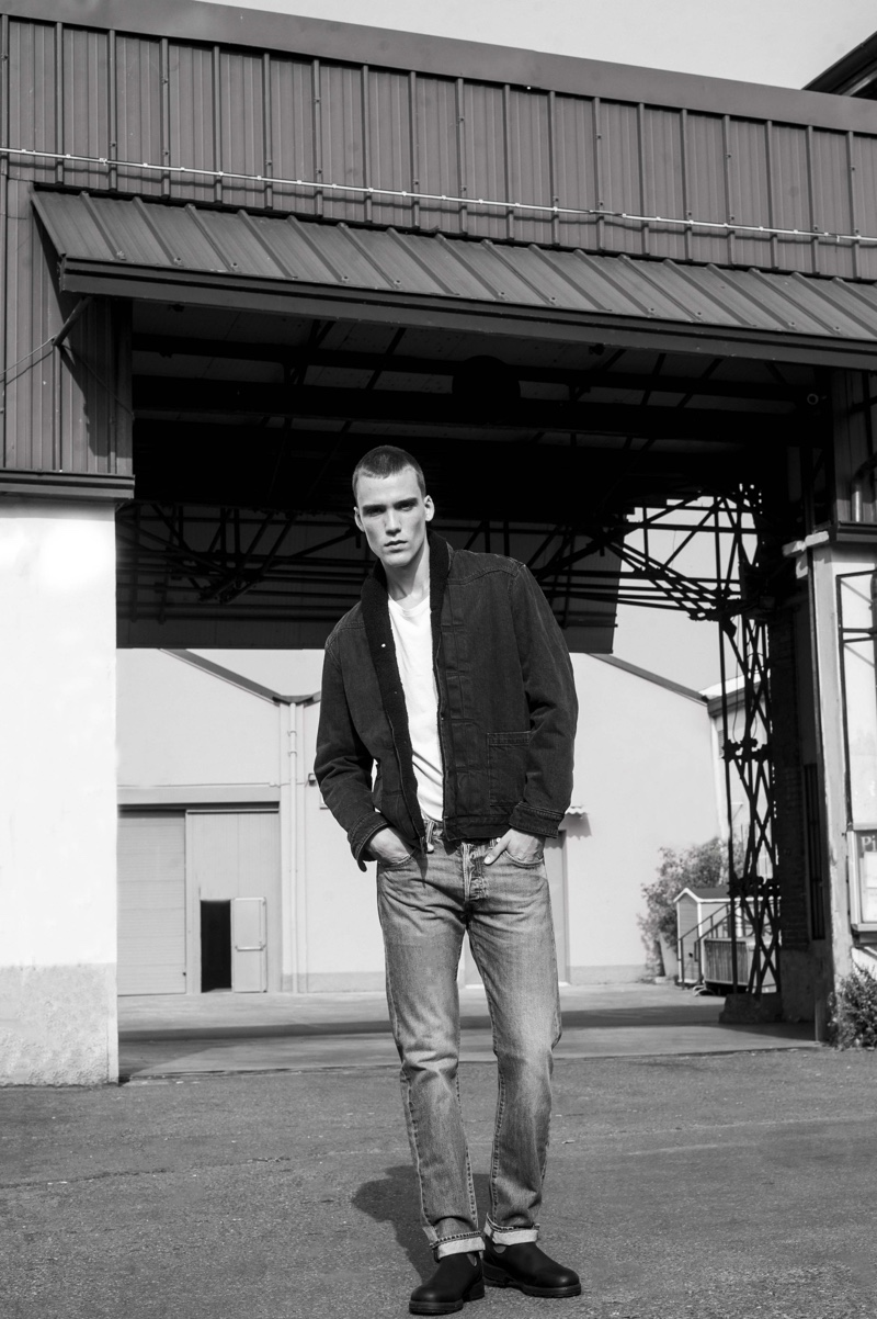 Sporting classic pieces by Levi's, Marc Lüloh wears a jacket, white tee, and distressed denim jeans.