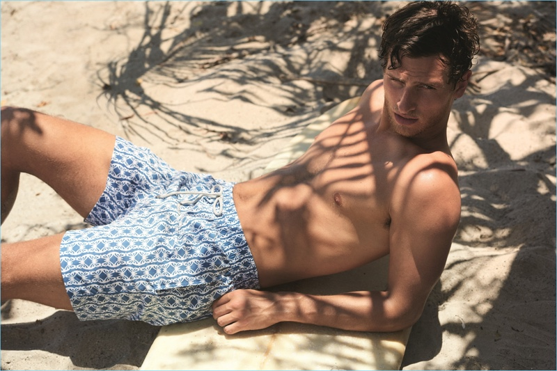 Relaxing at the beach, Tom Warren wears The Butterfly & The Caterpillar swim shorts from Love Brand & Co.
