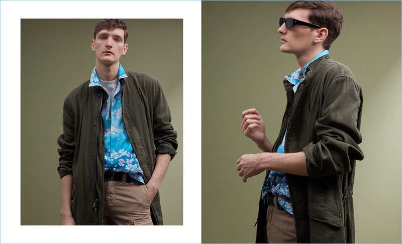 Model Yannick Abrath wears a Blue Blue Japan print short-sleeve shirt $500, Martine Rose logo-print t-shirt $173, and a Vince parka $700. The Belgian model also dons a Paul Smith leather belt $150, Incotex cargo shorts $287, and Stella McCartney sunglasses.