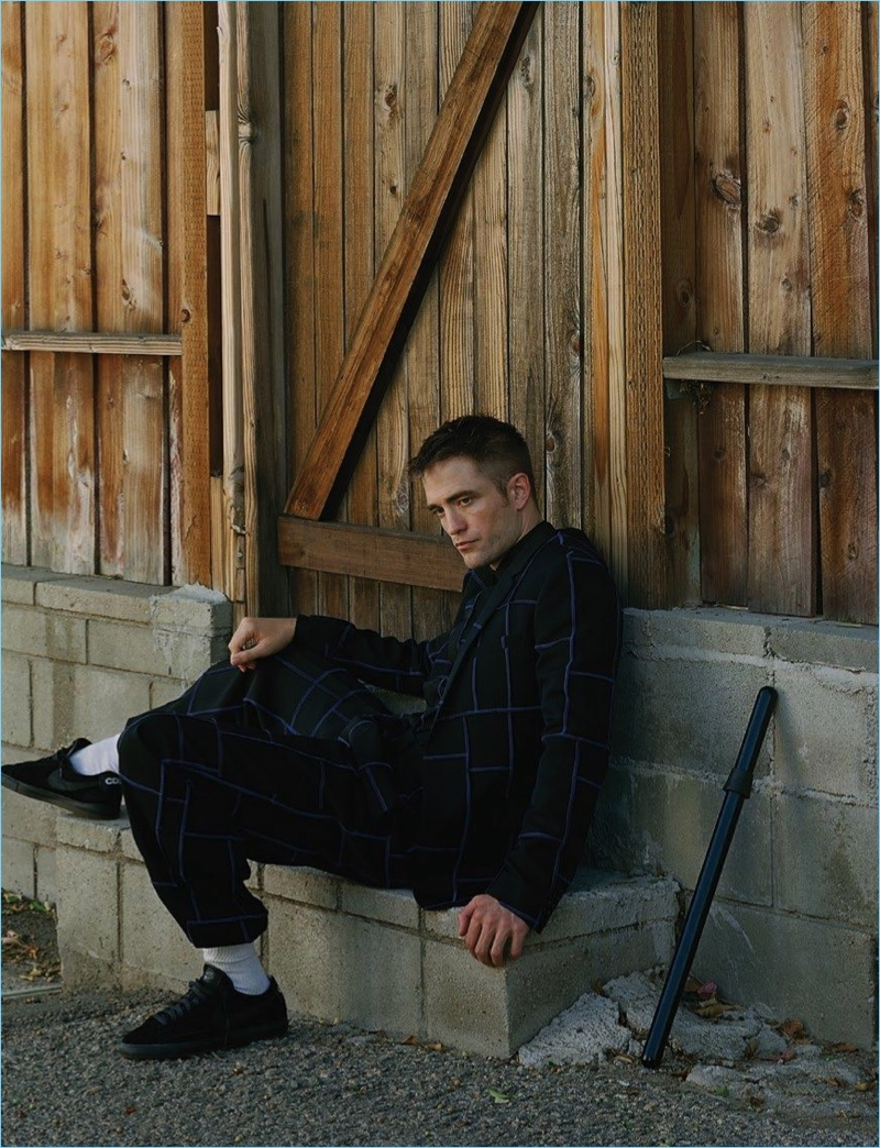 Venturing outdoors, Robert Pattinson wears an oversize check Dior Homme suit with his own sneakers.