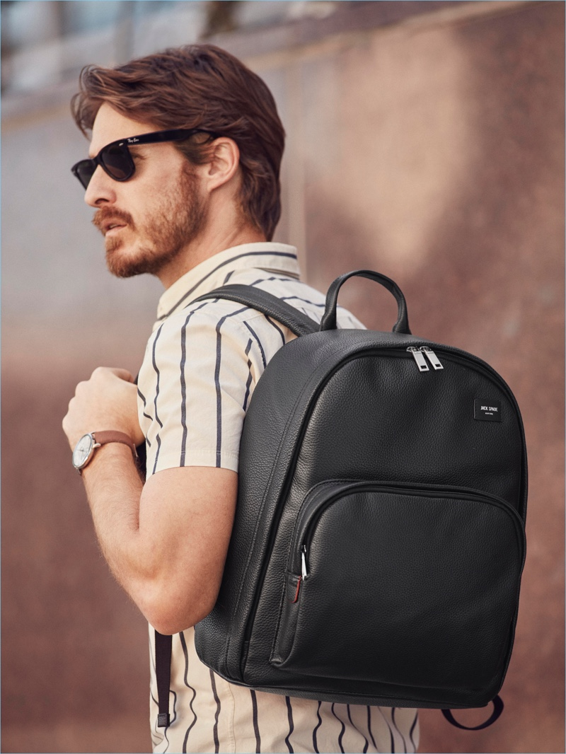 Heading out, Ryan Burns grabs a Jack Spade leather backpack.
