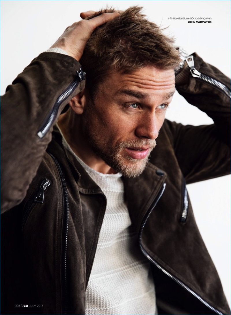 Delivering a side profile, Charlie Hunnam wears a suede biker jacket with a sweater from John Varvatos.