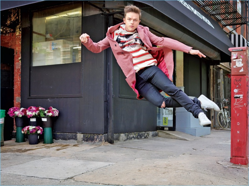 Leaping, Dane DeHaan wears a Stella McCartney t-shirt with a Prada overcoat. He also sports Saint Laurent jeans and Common Projects sneakers.