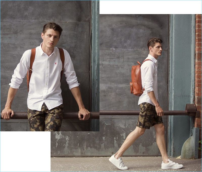 White Oxford: Eli Hall wears an AMI patch shirt $135 and Obey camouflage print shorts. He accessorizes with a Lotuff Leather backpack $1,100 and Buddy sneakers $255.