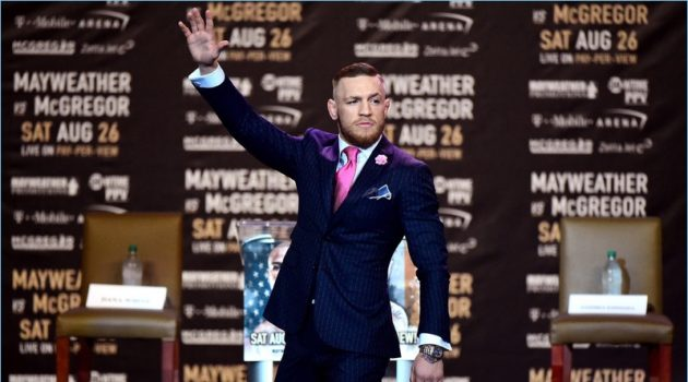 Conor McGregor makes his grand entrance to a press conference for his fight with Floyd Mayweather Jr.
