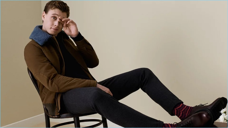 Ready for fall, George MacKay wears a Prada shearling-trimmed shell flight jacket $1,920. He also sports a Prada zip-detailed sweater $850, trousers $660, and leather oxford shoes $720.