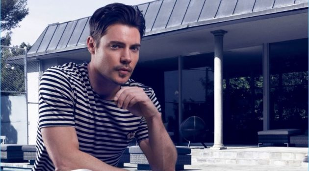 Relaxing outdoors, Josh Henderson wears a striped tee by The Kooples with AllSaints jeans, and Joseph Abboud dress shoes.