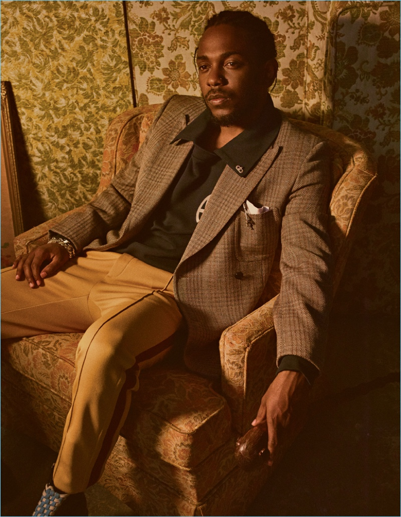 Appearing in an Interview shoot, Kendrick Lamar wears a Stella McCartney blazer and Gosha Rubchinskiy polo. He also sports a Neil Barrett pocket square, Coach side stripe trousers, and Gucci boots.