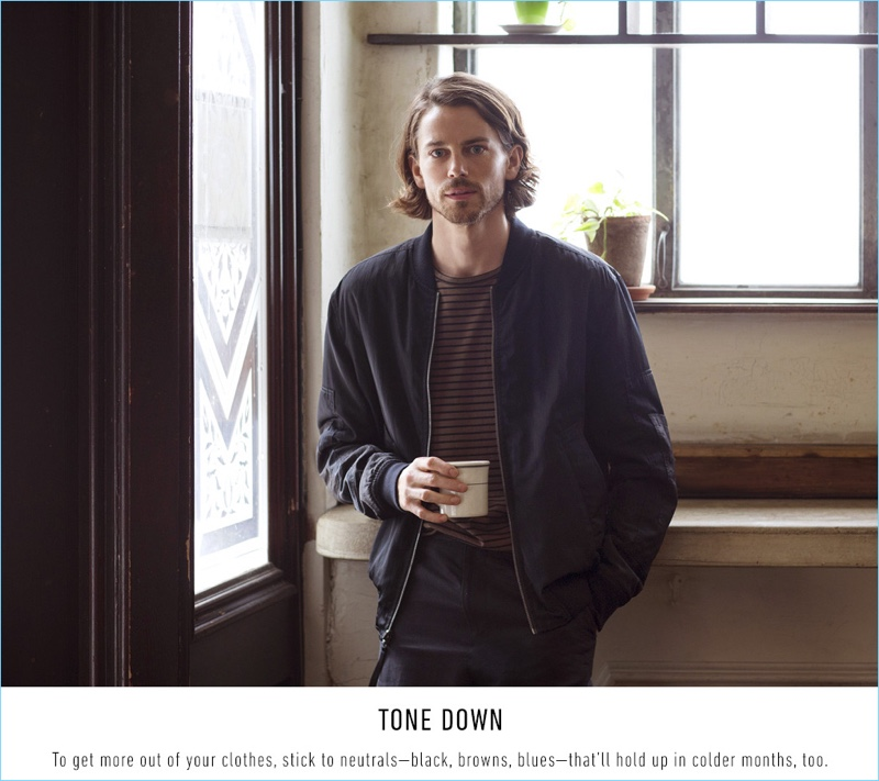 Enjoying a cup of coffee, Jeremy Young wears a Vince stripe tee $95, reversible bomber jacket $650, and drop crotch trousers $325.