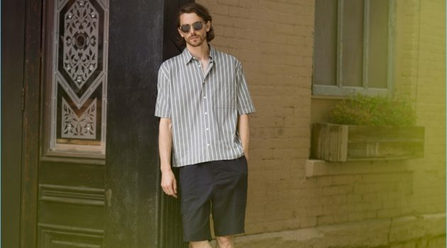 A summer vision, Jeremy Young wears a Vince stripe short-sleeve shirt $225, shorts $285, and slide sandals $95 with Paul Smith sunglasses $310.