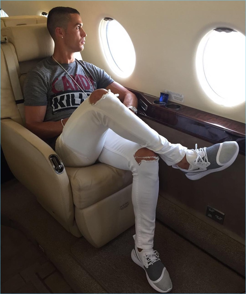 Traveling in luxury, Cristiano Ronaldo wears a pair of ripped white denim jeans from his CR7 range.