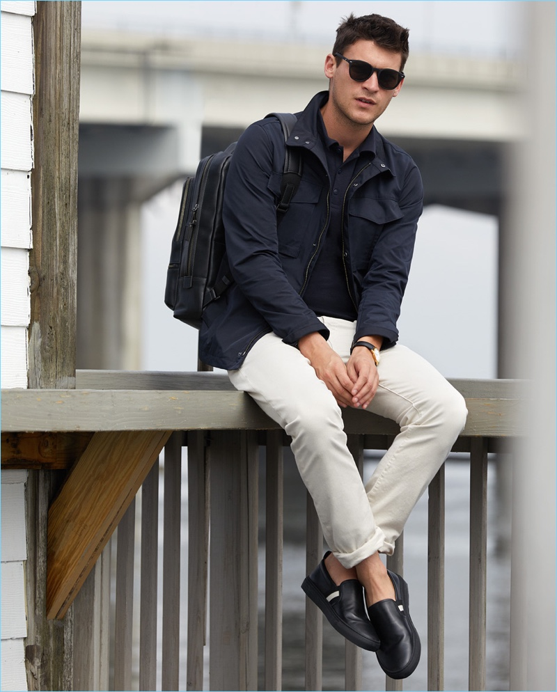 It's About Timeless: Miles Garber rocks a Theory field jacket $495 with a polo $70 by The White Briefs with J Brand slim-fit jeans $198. The model also wears a Tumi backpack $595, Bally slip-on sneakers $395, a Uniform Wares watch $600, and Le Specs sunglasses $69.