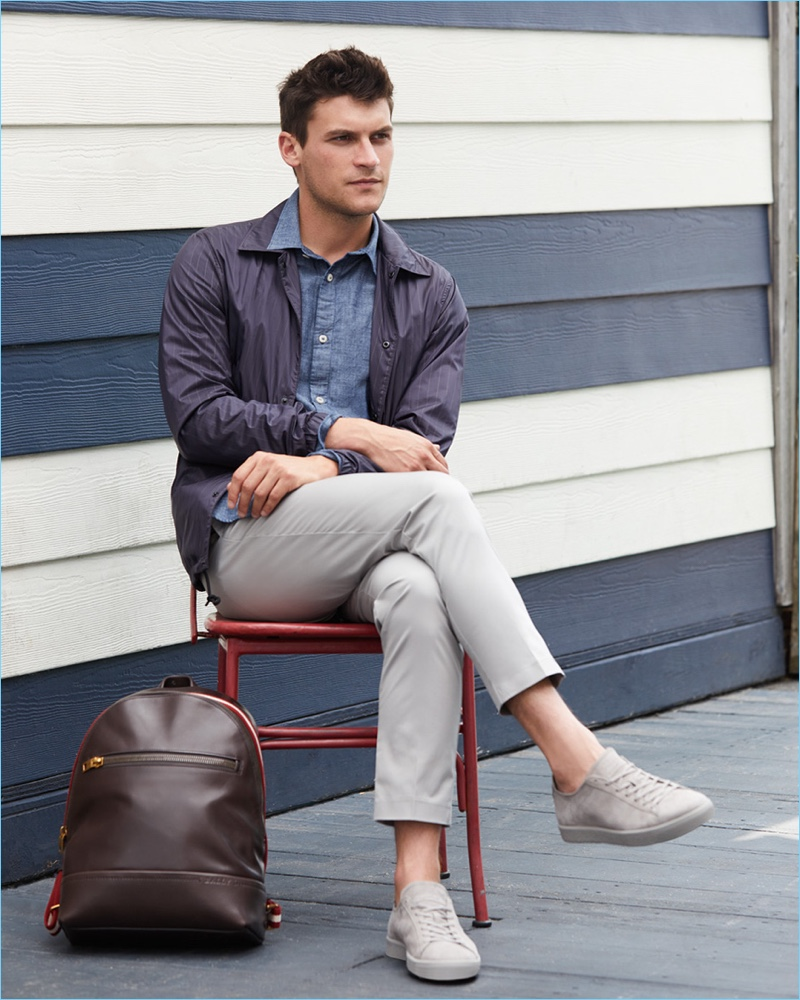 Relaxing, Miles Garber wears an Our Legacy chambray shirt $150 with a Theory pinstripe coach jacket $395 and cropped trousers $245. He also models a Jack Spade leather backpack $398 with To Boot New York suede sneakers $350.