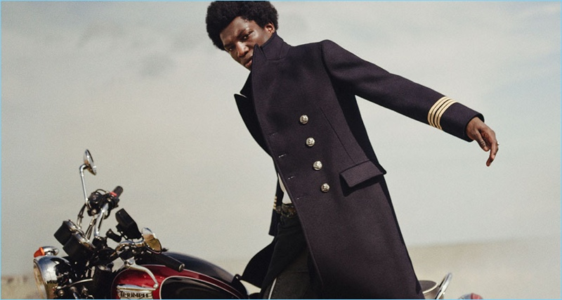 Model Josue Comoe connects with Farfetch for a fashion editorial. He wears a sharp officer coat by Gucci with an Alexander McQueen sweater. The model also sports John Lawrence Sullivan jeans with an Avant Toi scarf worn as a belt.