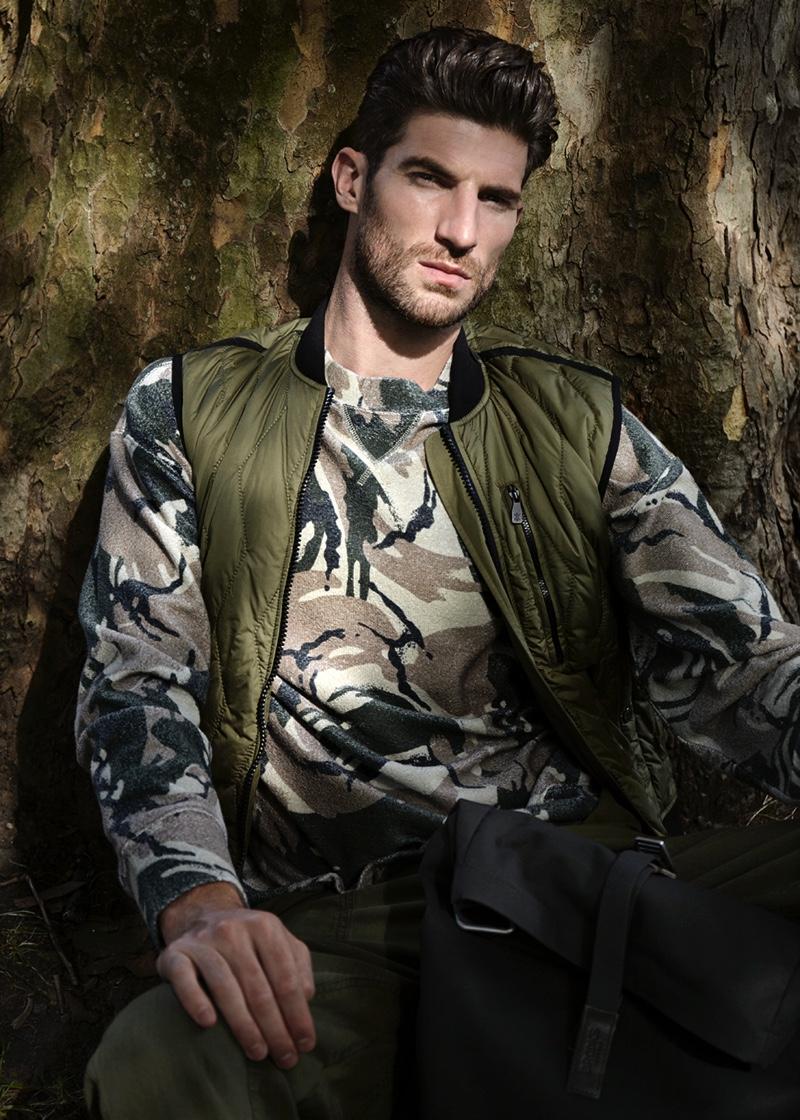 Ryan wears quilted vest Christopher Raeburn, camouflage print sweatshirt Weekday, herringbone trousers Y.M.C., and backpack Brooks.