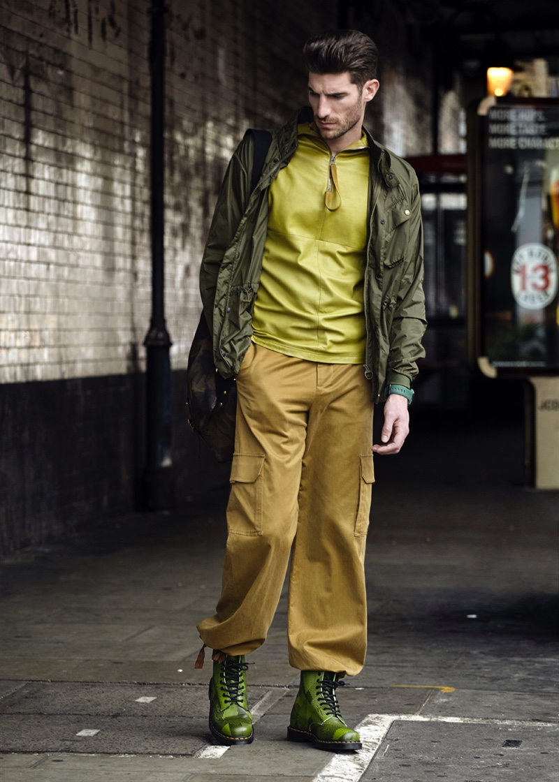 Ryan wears olive jacket Barbour, utility trousers, watch Nixon, and green leather top Qasimi. he also sports a camouflage bag and boots Dr Martens.