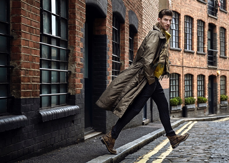 Ryan wears raincoat, sweater, and trousers Issey Miyake. He also rocks camouflage boots Dr Martens and scarf Spitalfield Market.