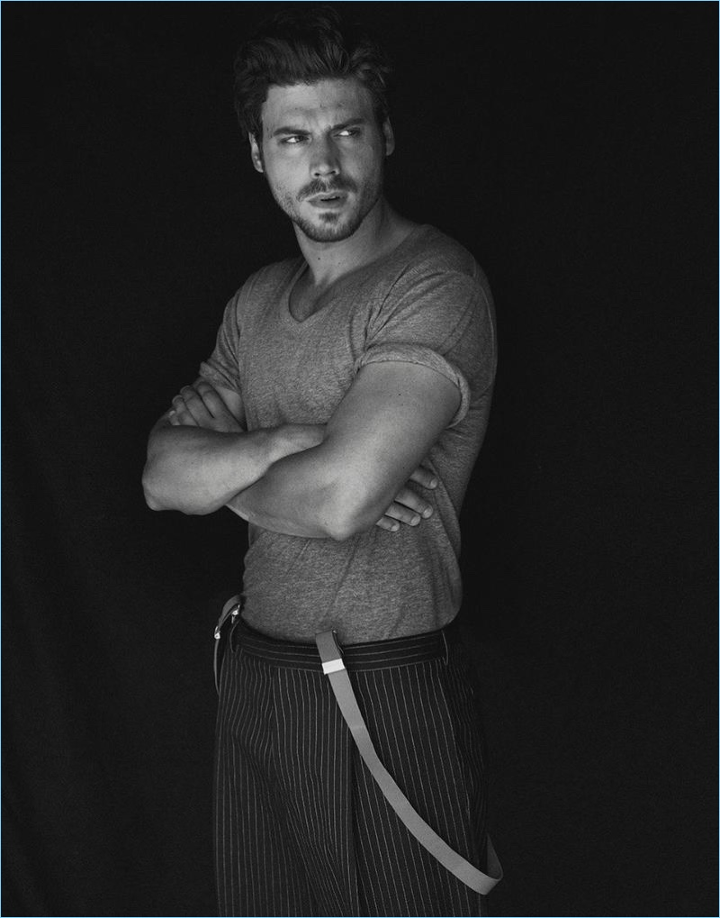 François Arnaud wears a T by Alexander Wang t-shirt with pinstripe Dior Homme trousers.