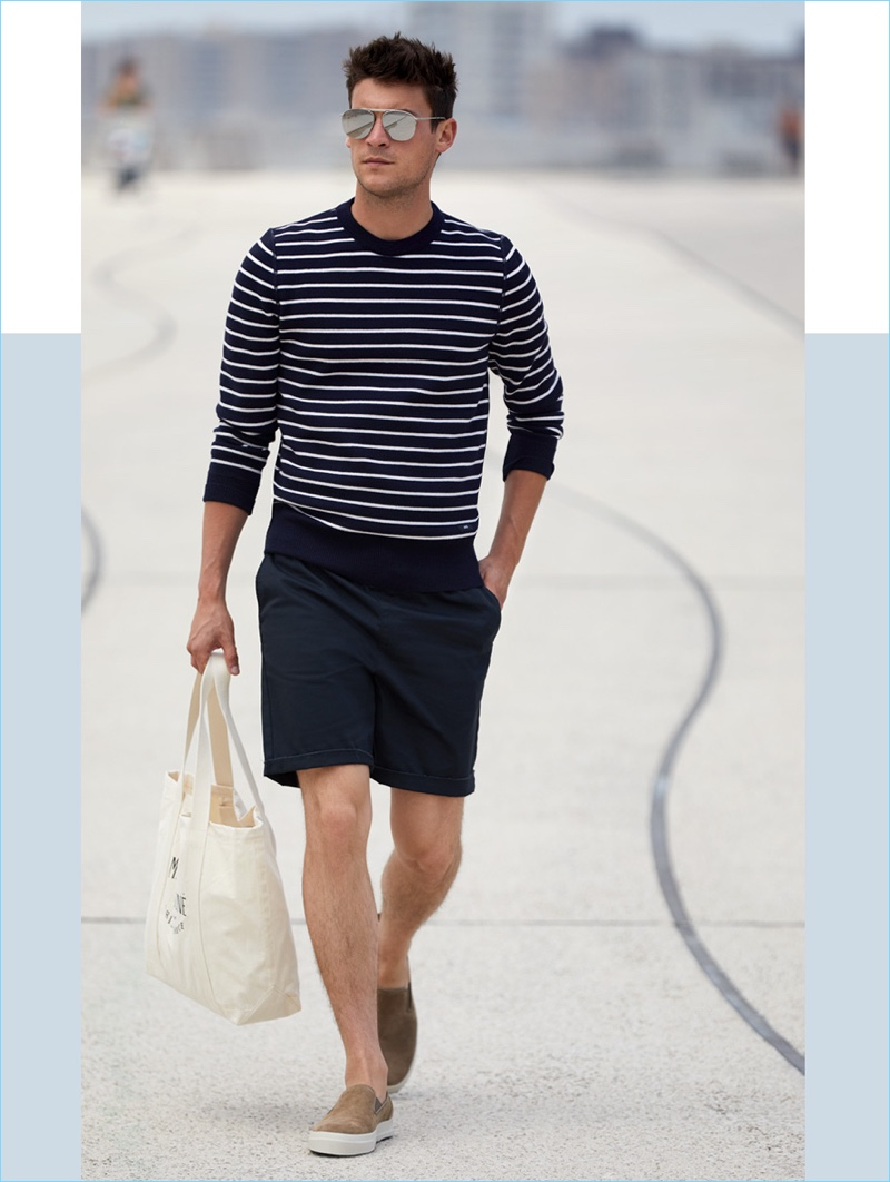 East Dane makes a case for shorts and knitwear. Embracing navy, Miles Garber wears an AMI striped sweater $200 with RVCA shorts $45. He also sports Vince suede slip-on sneakers $157.50, a Maison Kitsune tote bag $80, and Le Specs sunglasses $89.